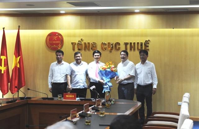 Ông Vũ Chí Hùng (đứng giữa) nhận hoa chúc mừng từ Tổng cục trưởng Tổng cục Thuế Cao Anh Tuấn.
