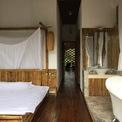 <p> Không gian tầng trên là 2 phòng ngủ liên tiếp, với nội thất mộc mạc, đặc trưng của vùng quê Việt Nam. Phòng ngủ chính có mặt tiền mở hoàn toàn, tạo không gian tiếp xúc trực tiếp với thiên nhiên. Sàn phòng ngủ có dầm nhịp đạt 4,5 m không có cột, phù hợp với không gian ăn uống mở bên dưới.</p>