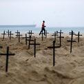 <p> Một người đàn ông chạy bộ qua hàng trăm ngôi mộ được các nhà hoạt động của tổ chức phi chính phủ Rio de Paz đào tại bãi biển Copacabana, Brazil vào ngày 12/6. Ảnh: <em>Reuters</em>.</p>