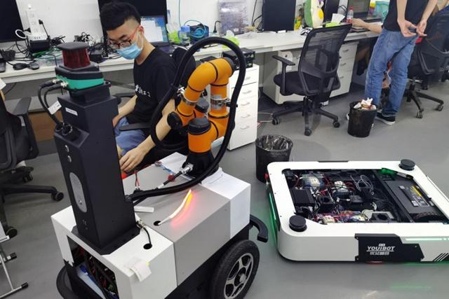 Do ảnh hưởng của Covid-19, một kỹ sư tại Youibot vừa đeo khẩu trang vừa làm việc với sản phẩm chỉ dẫn đi lại tự động tại phòng thí nghiệm của công ty, thành phố Thâm Quyến, tỉnh Quảng Đông, Trung Quốc ngày 25/05/2020. (Ảnh: Reuters)