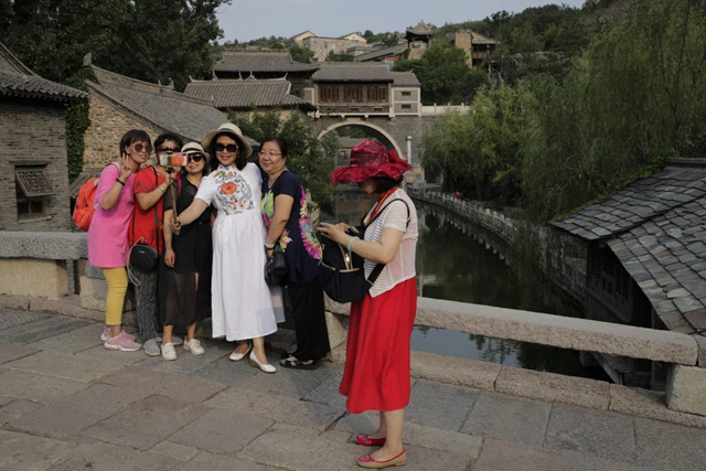 A group of women take a selfie against the ancient village in Gubei Water Town, a popular tourist spot in Beijing, on June 9. Some 59 per cent of mainland Chinese in a recent survey said they worry about travelling now, and a new outbreak of coronavirus has been reported in Beijing. Photo: Associated Press