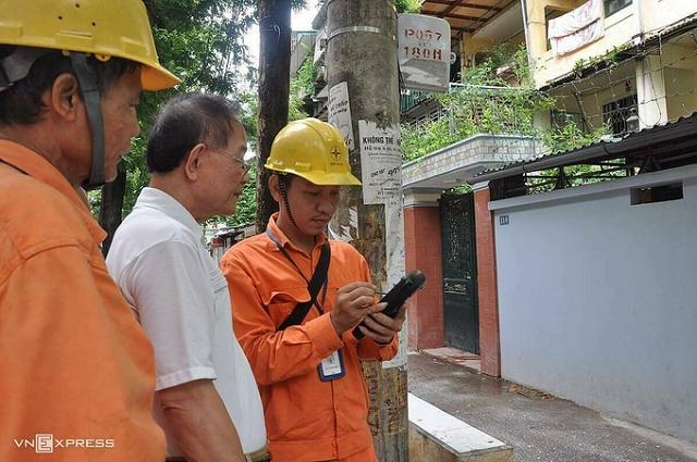 Nhân viên ngành điện đo công tơ điện tử bằng thiết bị đo từ xa. Ảnh: Anh Minh..