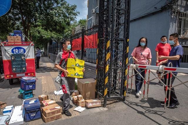 Nhân viên giao hàng tới một khu vực bị phong tỏa ở Bắc Kinh vì Covid-19. Ảnh: