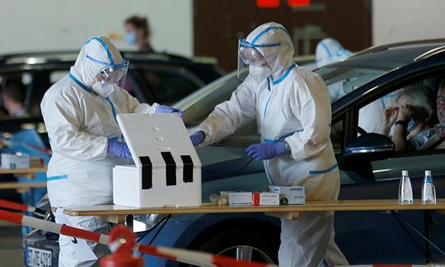 Nhân viên y tế lấy mẫu xét nghiệm nCoV trong nhà chứa máy bay của sân bay Guetersloh, Đức, ngày 27/6. Ảnh: Reuters.