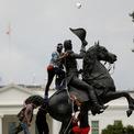 """<p class=""""Normal""""> Ngày 22/6, người biểu tình chống phân biệt chủng tộc tại Washington, Mỹ trèo lên nhằm tháo dỡ bức tượng của cựu Tổng thống Andrew Jackson nằm giữa Công viên Lafayette trước Nhà Trắng. Một số người ném các cuộn giấy vệ sinh lên tượng đài này. Ảnh: <em>Reuters</em>.</p>"""