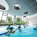 <p> Khối nhà công cộng có một bể bơi cho trẻ luyện tập. Đặc điểm nổi bật của công trình là những đường cong uốn lượn và cửa sổ hình tròn. Các ô cửa sổ có kích thước không giống nhau, được định vị tự do, ngẫu hứng, đáp ứng nhu cầu của các nhóm tuổi khác nhau.</p>