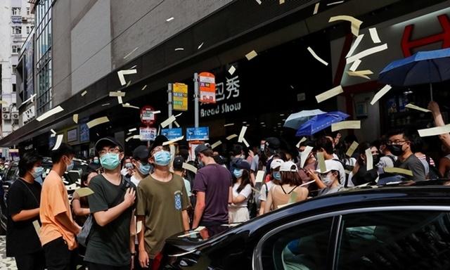 Người biểu tình tung tiền âm phủ trong cuộc tuần hành phản đối luật an ninh hôm 1/7. Ảnh: Reuters.