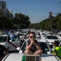 <p> Một cậu bé ngồi trên nóc xe taxi trong buổi biểu tình ở thành phố Madrid, Tây Ban Nha vào ngày 30/6. Các tài xế taxi tại thành phố này đang yêu cầu chính phủ hỗ trợ trong bối cảnh nhu cầu đi lại của người dân quá thấp vì dịch Covid-19. Ảnh: <em>AP</em>.</p>