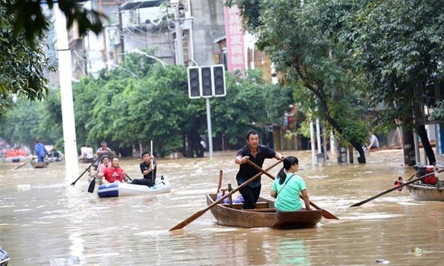 Người dân dùng thuyền để di chuyển vì lũ lụt tại huyện Dung Thủy, tỉnh Quảng Tây, hôm 11/7. Ảnh: Xinhua.