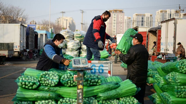 People wearing face masks move packs of vegetables at a wholesale market for agricultural products, as the country is hit by an outbreak of the novel coronavirus, in Beijing, China February 19, 2020.