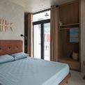 """<p> """"Mùi biển"""" thể hiện qua việc lựa chọn màu sắc và chất liệu, như màu vàng cát của bê tông đánh bóng, tường và trần nhà; màu nâu gỗ của rèm cửa, thảm; màu xanh lá cây của bồn tắm bê tông, đồ gốm...</p>"""