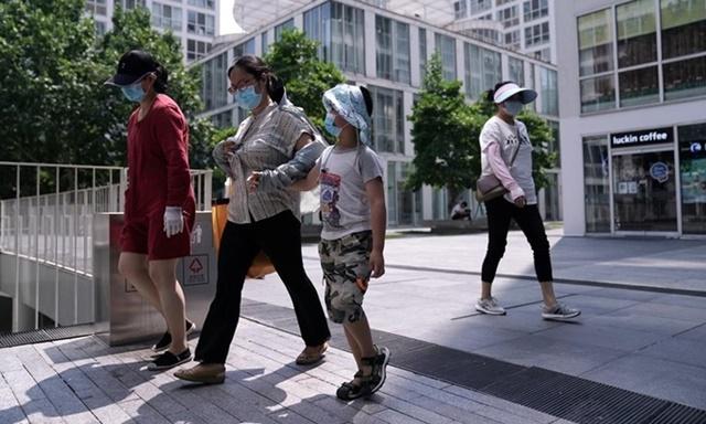 Người dân đeo khẩu trang đi qua khu phức hợp thương mại và văn phòng ở Bắc Kinh, Trung Quốc hôm 23/7. Ảnh: Reuters.