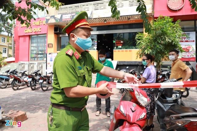 Cảnh sát chăng dây phong tỏa quán pizza có ca nghi nhiễm. Ảnh: Hồng Quang.