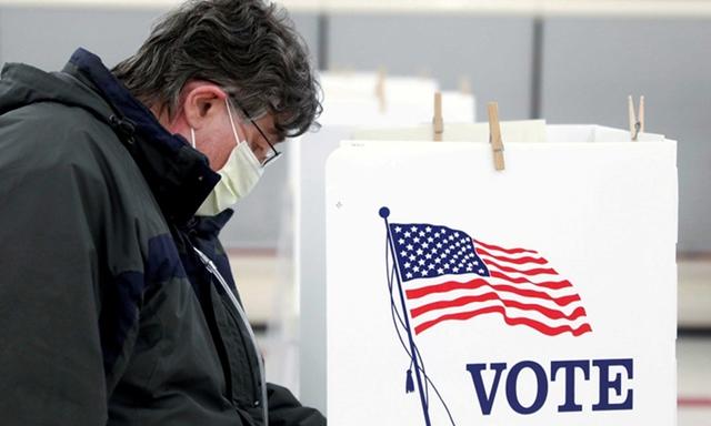 Một cử tri đeo khẩu trang đi bỏ phiếu bầu cử sơ bộ ở Ottawa, bang Illinois, hồi tháng 3. Ảnh: Reuters.