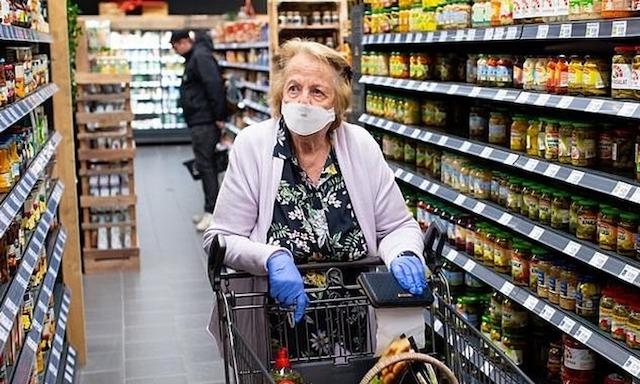 Một khách hàng đeo khẩu trang và găng tay đi siêu thị tại Đức. Ảnh: Hoppe.