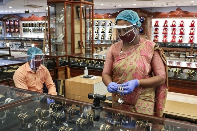 Một phụ nữ Ấn Độ đem vàng đi bán tại một cửa hàng ở thành phố Kolkata. Ảnh: WSJ.