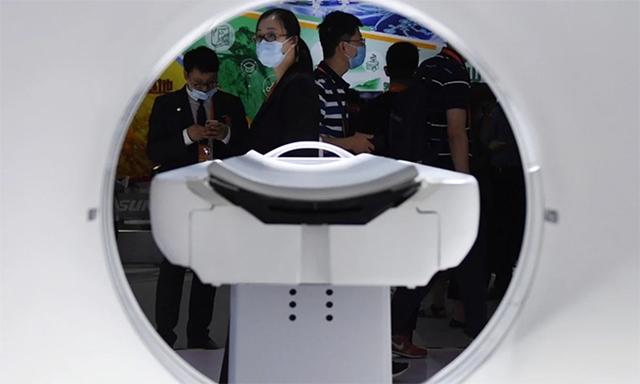 Khách tham quan xem máy chụp cắt lớp được trưng bày tại một triển lãm ở Bắc Kinh, Trung Quốc, ngày 6/9. Ảnh: Xinhua.