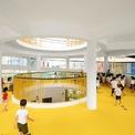 """<p class=""""Normal""""> Với yêu cầu tăng các không gian vui chơi và hoạt động thể chất cho trẻ em, các kiến trúc sư đã thiết kế một """"tháp vận động"""" với kết cấu hình xoắn ốc thu nhỏ dần ở phía trên và một lõi xanh trung tâm. Về mặt thẩm mỹ, """"tháp vận động"""" đã trở thành điểm nhấn thu hút trong tổng thể công trình trường học, đồng thời tạo nên một kết cấu cầu, giúp kết nối các lớp học chính với không gian vui chơi.</p>"""