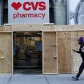 <p> Cửa hiệu thuốc CVS ở thành phố Boston, bang Massachusetts, vẫn mở cửa đón khách sau khi đã gia cố bằng ván gỗ. Ảnh: <em>AP.</em></p>