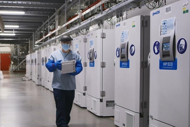 A worker passes a line of freezers holding coronavirus disease (COVID-19) vaccine candidate BNT162b2 at a Pfizer facility in Puurs, Belgium in an undated photograph. Pfizer/Handout via REUTERS