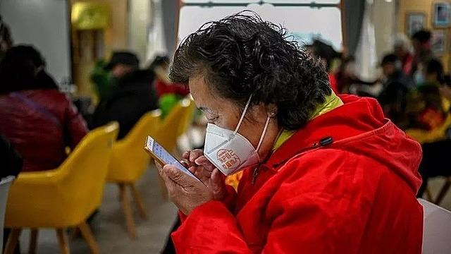 Một người già đang học cách dùng điện thoại thông minh ở Trung Quốc. Ảnh: AFP.