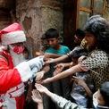 """<p class=""""Normal""""> """"Ông già Noel"""" xịt nước sát trùng cho các em nhỏ tại một khu ổ chuột ở Mumbai, Ấn Độ, trước khi phát quà.</p>"""