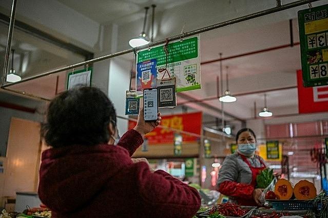 Một người già quét QR thanh toán tiền mua rau củ tại Thành Đô, Tứ Xuyên. Ảnh: AFP.