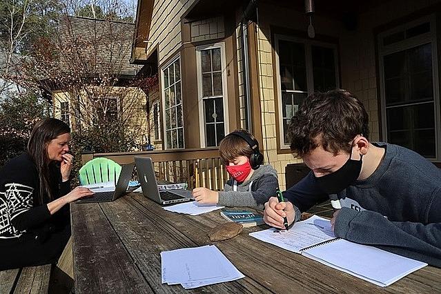 Một gia đình làm việc và học tập bên ngoài căn nhà ở Oxford, Mississippi (Mỹ). Ảnh: AP.
