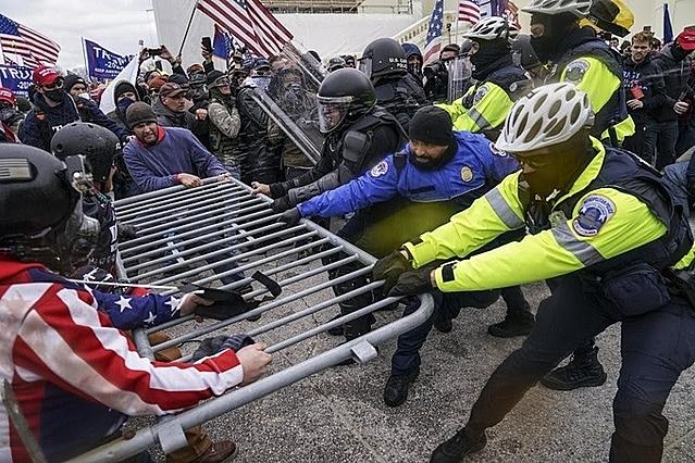 Người ủng hộ Trump đạp đổ rào chắn bên ngoài Điện Capitol ngày 6/1. Ảnh: AP.