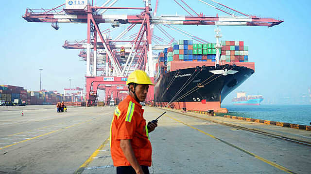 A Chinese worker looks on as a cargo ship is loaded at a port in Qingdao, eastern China's Shandong province.
