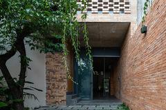 Nhà được bao phủ bởi nhiều lớp gạch thô và cây xanh