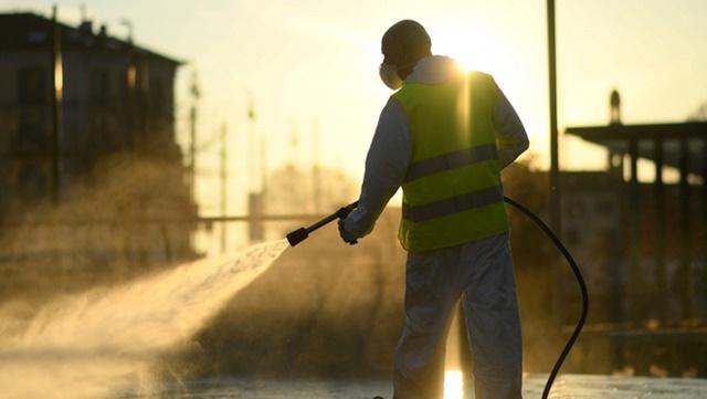 Một công nhân khử trùng đường phố Milan, Italia, trong đợt phong tỏa hồi tháng 3/2020. Ảnh: Reuters.
