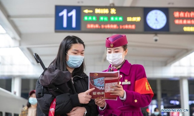 Một nhân viên phát tờ rơi về phòng chống dịch Covid-19 cho hành khách ở nhà ga Trùng Khánh hôm 25/1. Ảnh: Xinhua.