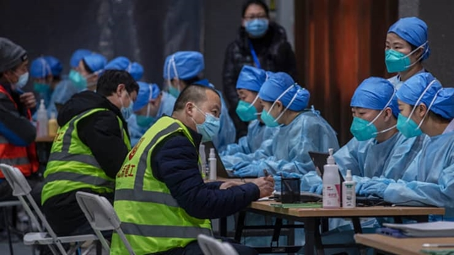 Chinese health care workers and volunteers wear protective clothing as they register people to receive a Covid-19 vaccine jab at a mass vaccination center for Chaoyang District on January 15, 2021 in Beijing, China.