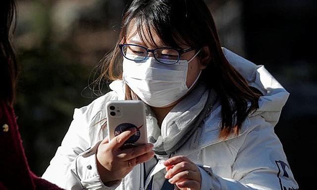 Một người dùng iPhone khi đang đeo khẩu trang ở New York. Ảnh: Reuters.