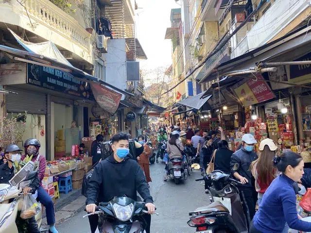 """Tại Hà Nội, không khí mua sắm khẩn trương, nhộn nhịp kéo dài suốt những ngày cuối năm. Đoạn phố ngắn tập trung nhiều cửa hàng bánh kẹo, rượu bia """"tê liệt"""" vì khách sắm tết. Cửa hàng mở cửa sớm hơn thường lệ, phục vụ khách ngày 30 Tết"""