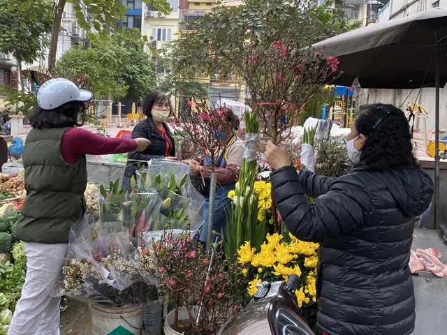 Tiểu thương không ngơi tay bó hoa trong buổi chợ cuối năm. Đây cũng là mặt hàng hết sớm trong sáng 30 Tết. Trong khi đào rớt giá thê thảm, 30.000 – 100.000 đồng/ cành thì các loại hoa cắm chơi như ly, lay ơn, thược dược, violet tăng chóng mặt. Ly kép lên đến 50.000 đồng/ cành
