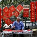 """<p class=""""Normal""""> Một cụ ông ngồi viết thư pháp trên giấy đỏ để bán trên một tuyến phố ở Hong Kong, Trung Quốc. Ảnh:<em> Reuters.</em></p>"""