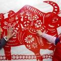 <p> Nghệ sĩ Zheng Shulin bên cạnh tranh cắt giấy hình con trâu đón năm 2021 của ông tại Thượng Hải, Trung Quốc. Ảnh: <em>SCMP.</em></p>