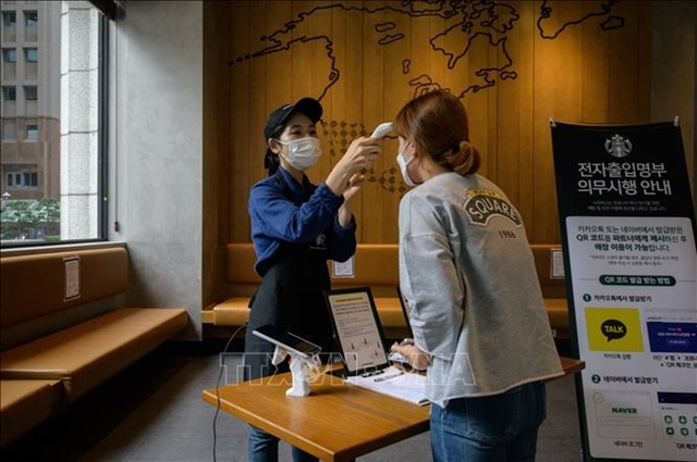 Đo thân nhiệt nhằm ngăn chặn sự lây lan của dịch COVID-19 tại thủ đô Seoul, Hàn Quốc. Ảnh: AFP/TTXVN