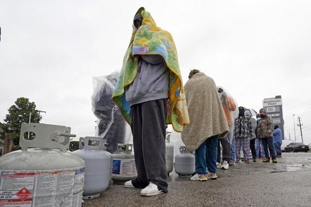 Người dân Texas quấn chăn xếp hàng đợi nạp gas dùng cho máy sưởi ở Houston, Texas hôm 17/2. Ảnh: AP.