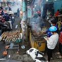 """<p class=""""Normal""""> Từ đêm 20 đến sáng 21/2, đường Tân Kỳ Tân Quý (quận Tân Phú, TP HCM) nghi ngút khói từ hàng chục gian hàng nướng, bày bán cá lóc ngày vía Thần tài (mùng 10 tháng Giêng).</p> <p class=""""Normal""""> Tại gian hàng của ông Nguyễn Trung, tấp nập người nướng gần 4 tấn cá lóc. """"Bảy năm theo nghề này, cứ mỗi năm là số cá nướng tăng lên. Năm ngoái nướng hơn 2 tấn nhưng năm nay là gần 4.000 con, mỗi con hơn một kg, nên phải huy động 30 người, gồm anh em và thuê thêm nhân công nướng mới kịp"""", ông Trung, chủ tiệm nói.</p>"""