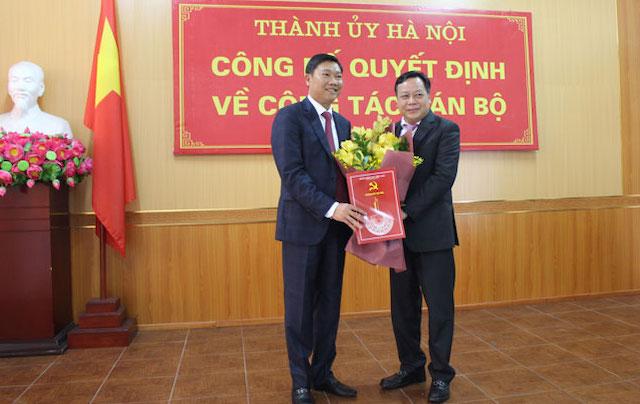 Phó Bí thư Thành ủy Hà Nội Nguyễn Văn Phong trao quyết định và tặng hoa chúc mừng đồng chí Đỗ Anh Tuấn.