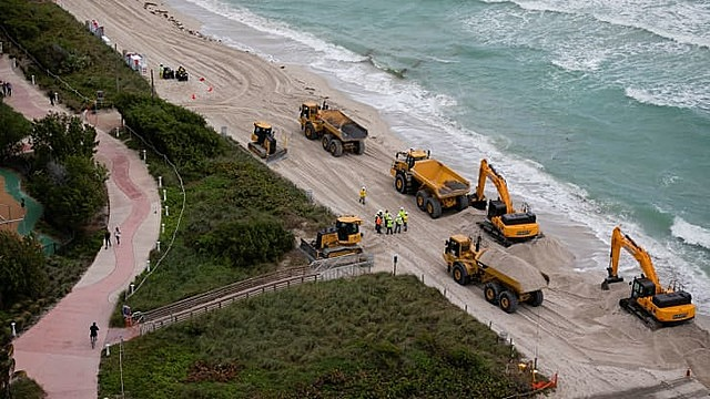Dozens of trucks dump hundreds of thousands of tons of sand on Miami Beach as part of U.S. government measures to protect Florida's tourist destinations against the effects of climate change.