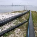 <p> Nhiều ống nhựa cỡ lớn dài hàng trăm mét nối từ trong bờ ra moong mỏ phục vụ thi công trước đây, hiện chưa thu dọn.</p>