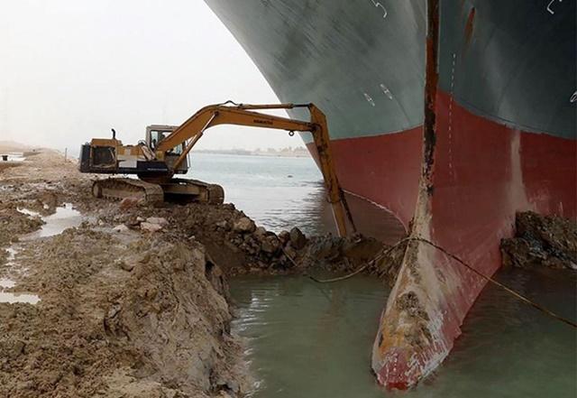Một chiếc máy xúc đang nạo vét quanh mũi tàu Ever Given. Ảnh: AFP.