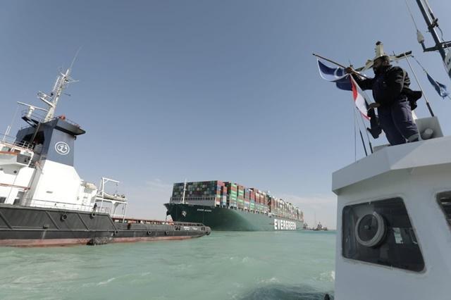 Người đàn ông vẫy cờ Ai Cập ăn mừng con tàu Ever Given thoát khỏi vụ mắc cạn. Ảnh: Reuters.