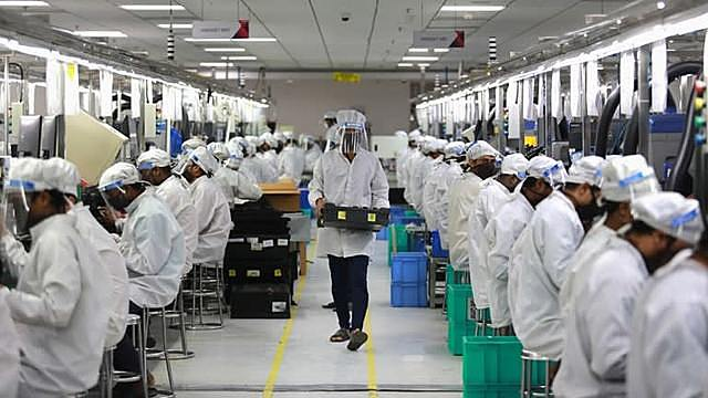 Workers with face shields keep a mobile phone assembly line humming in Noida, India, even during the country's coronavirus lockdown through May 2020.   © Reuters