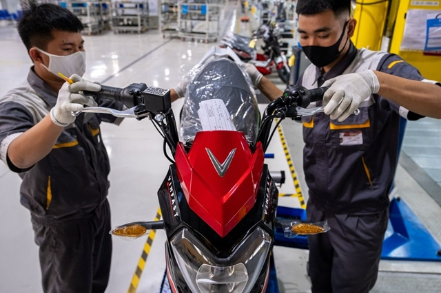 Workers labor on a VinFast Impes electric scooter on the assembly line of the automaker's factory in Haiphong, Vietnam. Photographer: Linh Pham/Bloomberg