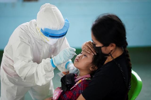 Nhân viên y tế Thái Lan lấy mẫu xét nghiệm Covid-19 cho một bé gái. Ảnh: Reuters.